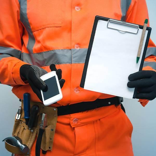 mężczyzna wubraniu roboczym trzymający wjednej dłoni telefon awdrugiej podkładkę zkartkami idługopisem